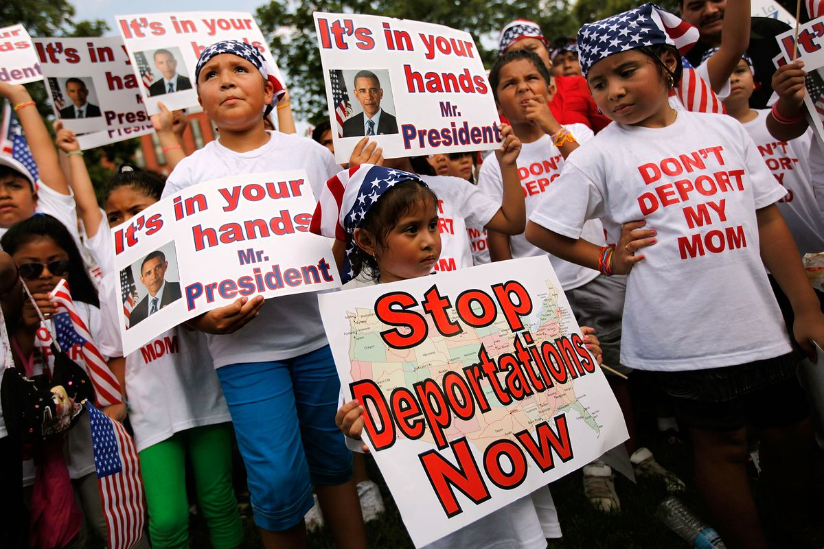 Children hold signs imploring President Obama to stop deportations.