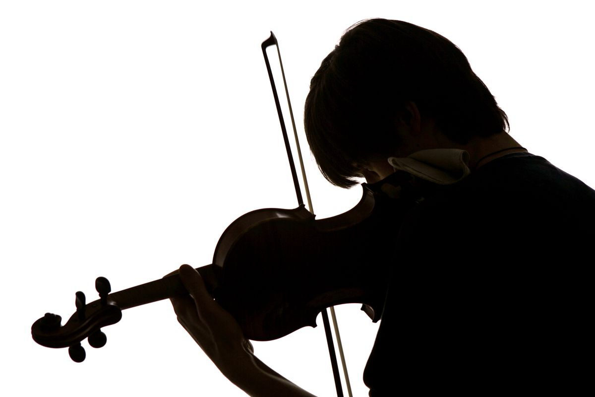 A silhouette of a student practicing the violin.