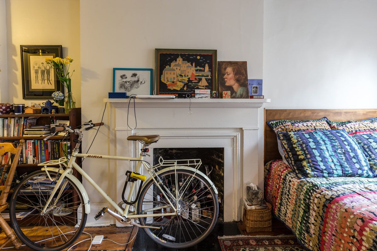 A living space with a fireplace, bicycle, bed with patterned bed linens, and works of art.