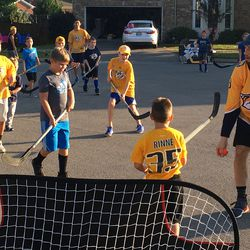 Nick Bonino tries to avoid a hand pass during an intense game of street hockey in Nolensville.