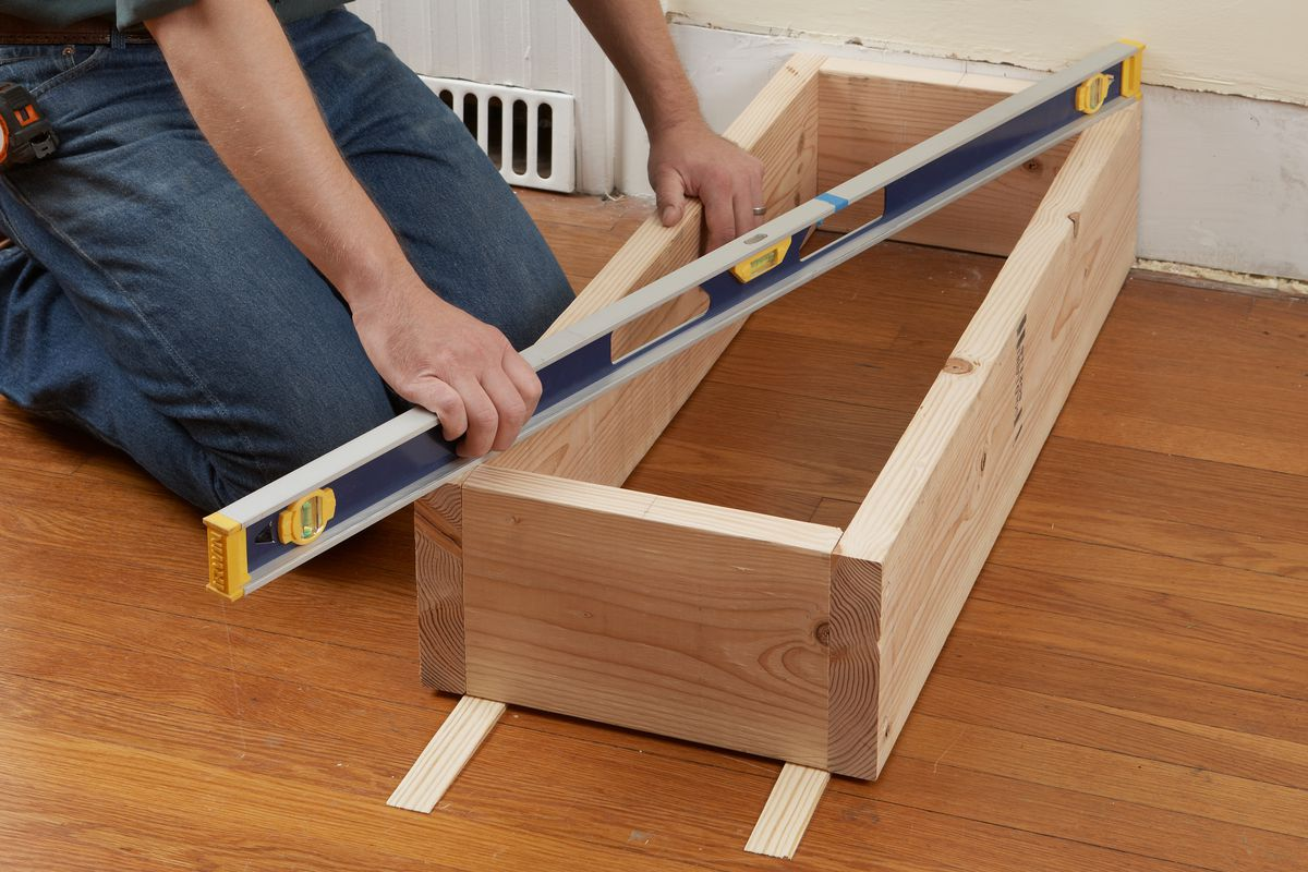 Man Using Level To Check Base Of Columned Room Divider