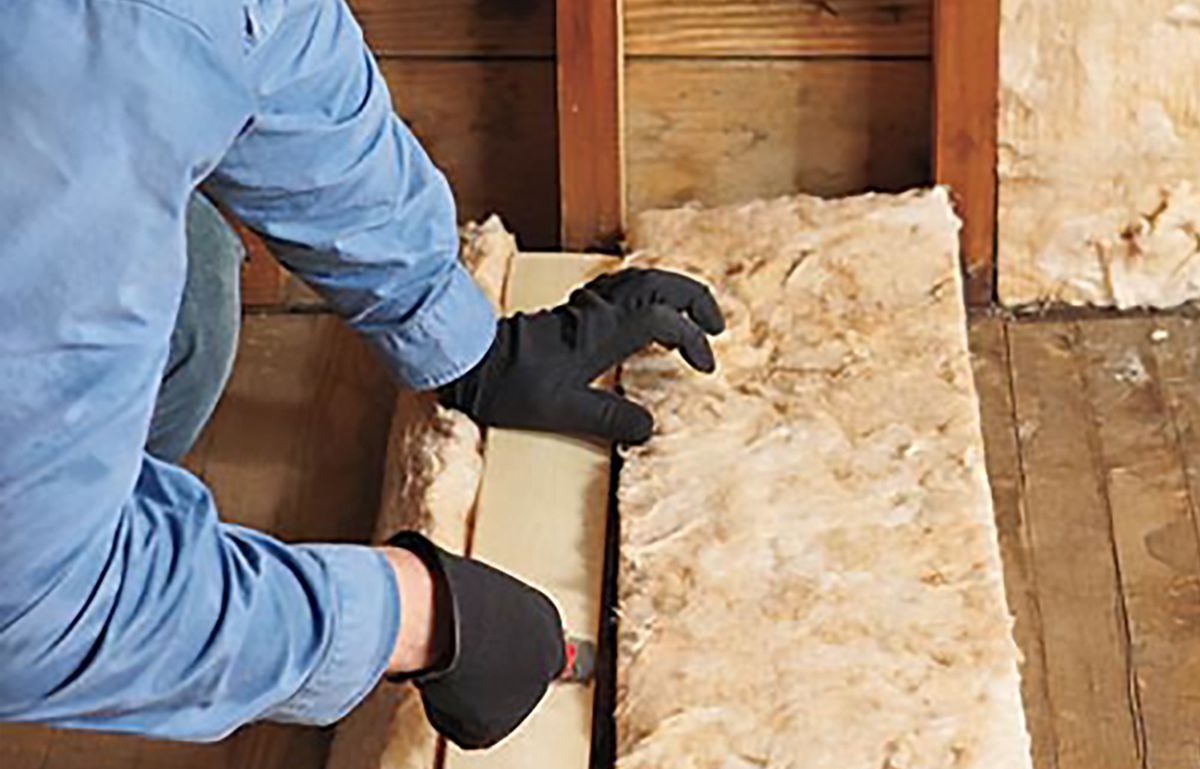 Man Trimming Insulation With Utility Knife