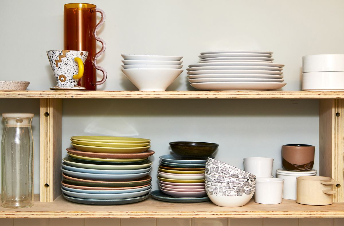 Two wooden shelves, with various colored plates, bowls, mugs and pitcher.