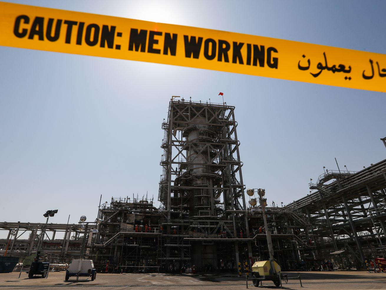 "Saudi Arabaian oil factory with yellow tape reading ""Caution: Men Working"""