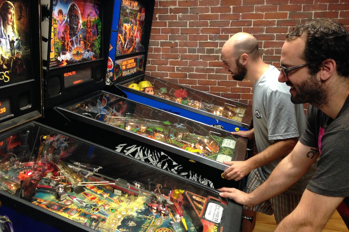 Dave Aceto (left) and Ben Culver test out pinball machines at Arcadia.