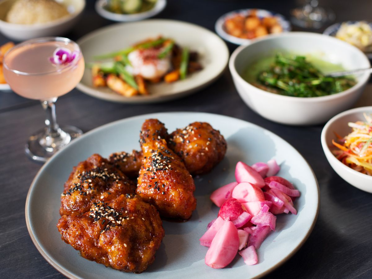 Wings with a side of pickled pink radishes, a pink cocktail in a cup, and more salads on the side.