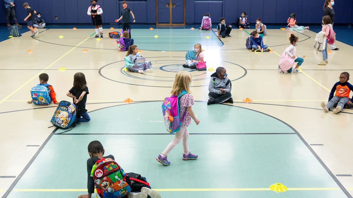 Students line up on colored dots by class in the school gym to wait for their rides after dismissal.