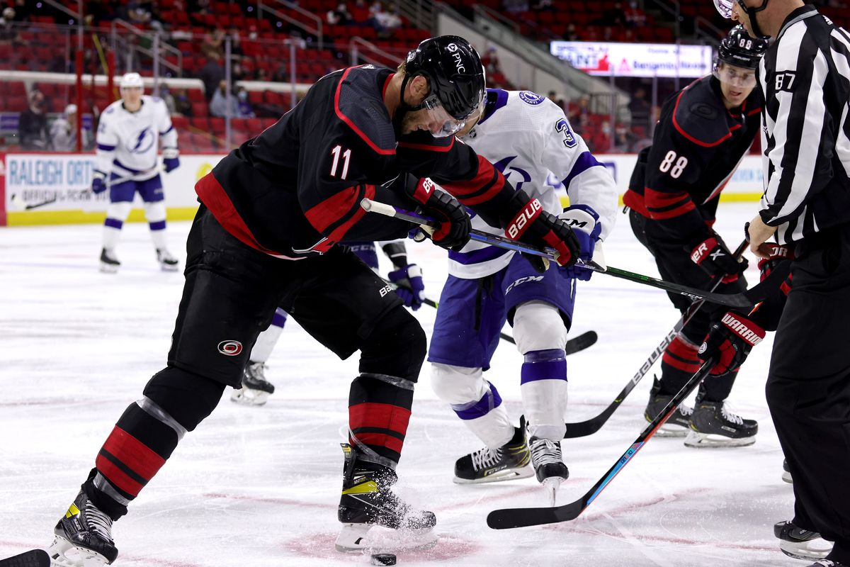 Jordan Staal #11 of the Carolina Hurricanes wins a face-off battle against Yanni Gourde #37 of the Tampa Bay Lightning during an NHL game on March 27, 2021 at PNC Arena in Raleigh, North Carolina.