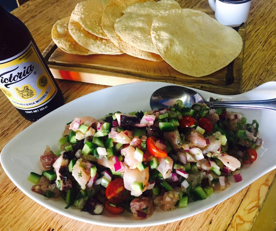 A long dish of ceviche beside a wood board loaded with tortillas and a bottle of beer