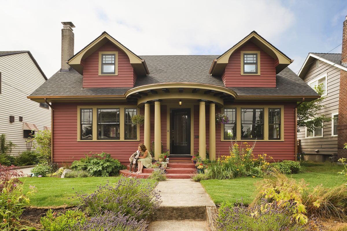 A burgundy house with a porch enclosed by columns.
