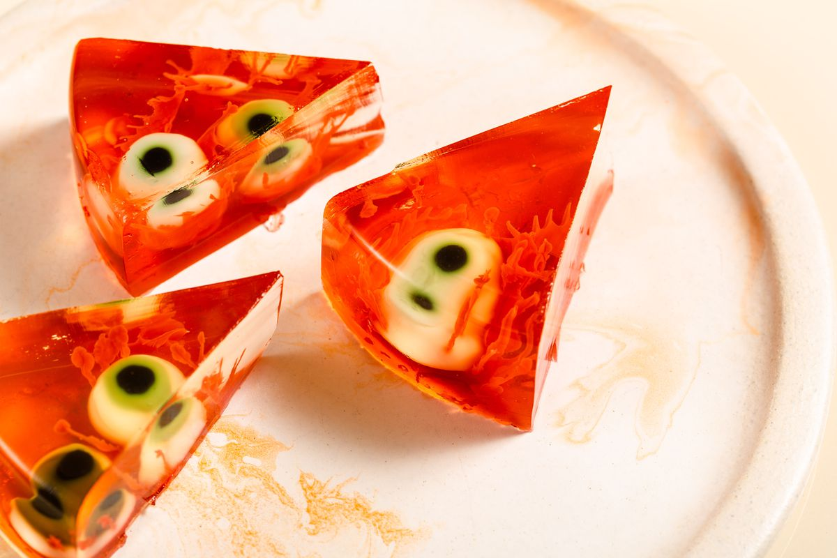 Three slices of a red jelly cake filled with fake eyeballs and booze sit on a cream-colored plate.