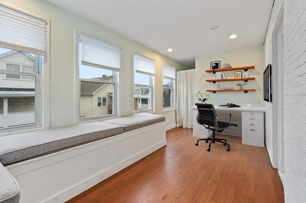 A long office with a desk and a chair at the end and a bench seat with cushions.