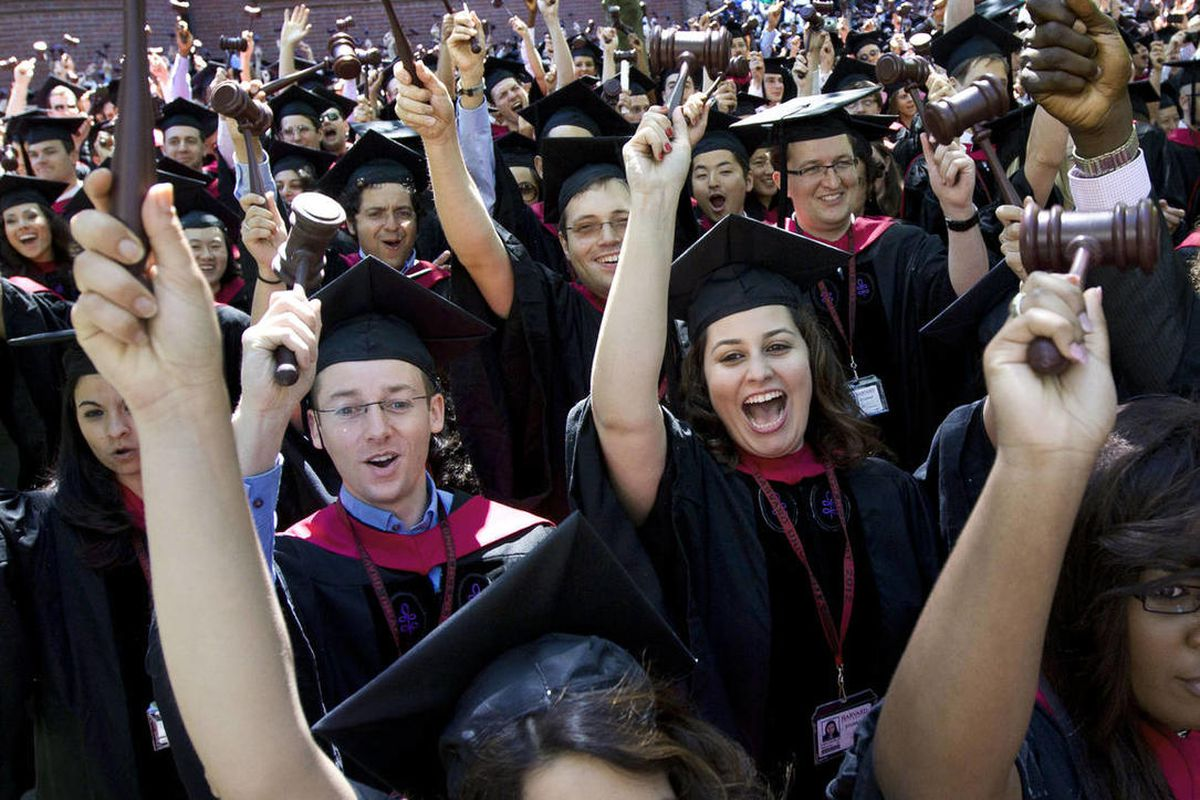 Graduates of Harvard Law School wave gavels as their degrees are conferred during Harvard University commencement exercises, in Cambridge, Mass., Thursday, May 24, 2012.