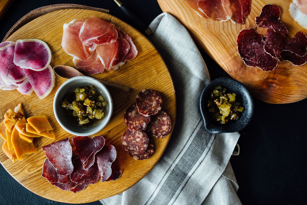 a charcuterie spread on a round, wooden plate