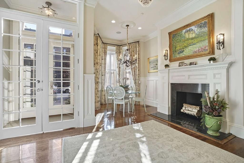 A sitting room next to some glass French doors and with a table with chairs and a fireplace.