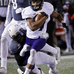 Weber State Wildcats running back Kevin Smith makes a long run and is tackled by Southern Utah Thunderbirds linebacker Kyle Tauiliili during NCAA football in Cedar City on Saturday, Dec. 2, 2017.