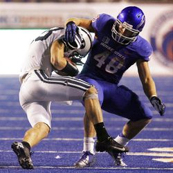 Riley Nelson of the Brigham Young Cougars is tackled by J.C. Percy of the Boise State Broncos during NCAA football in Boise, Thursday, Sept. 20, 2012.