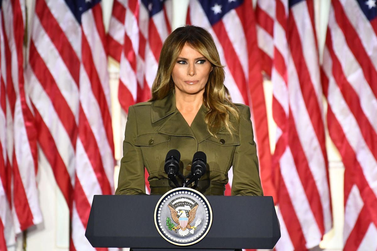 Melania Trump stands before a podium, backed by American flags.