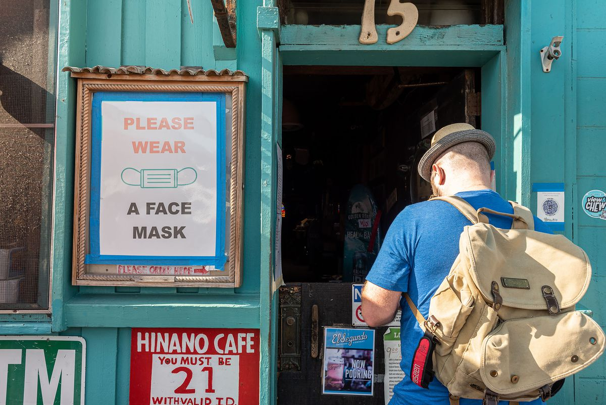 A customer waits for a drink in front of a mask mandate sign at a teal dive bar.