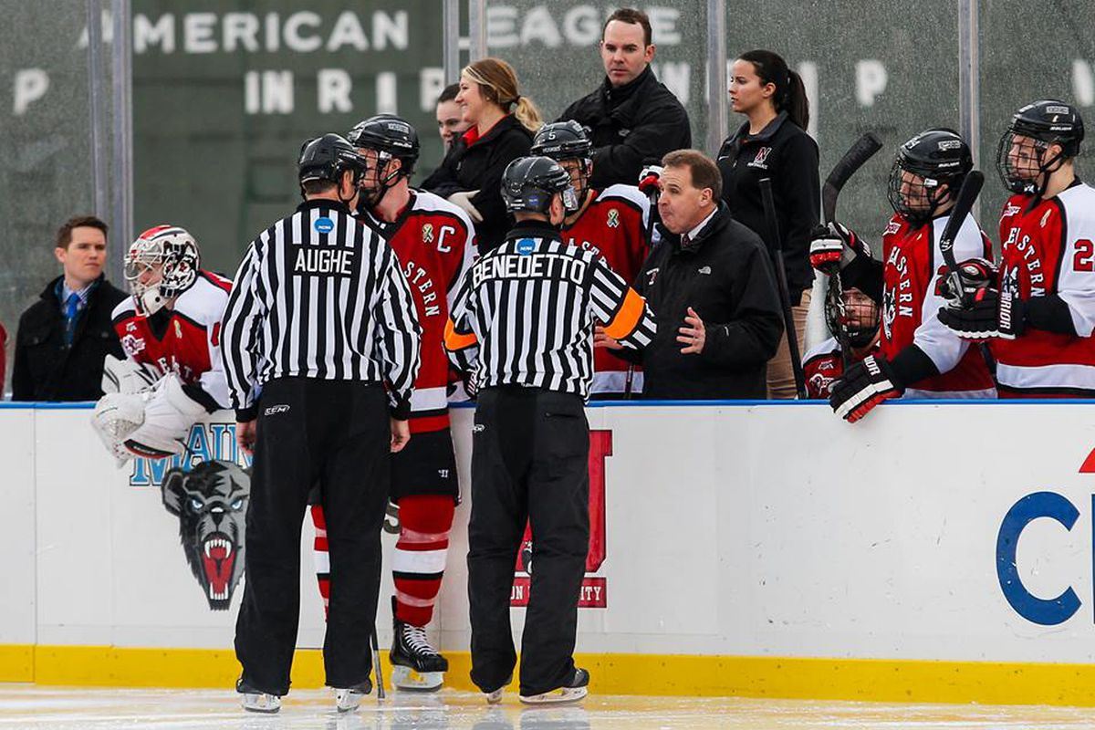 Jim Madigan disagrees with Hockey East officials Tim Benedetto and Chris Aughe at Frozen Fenway.