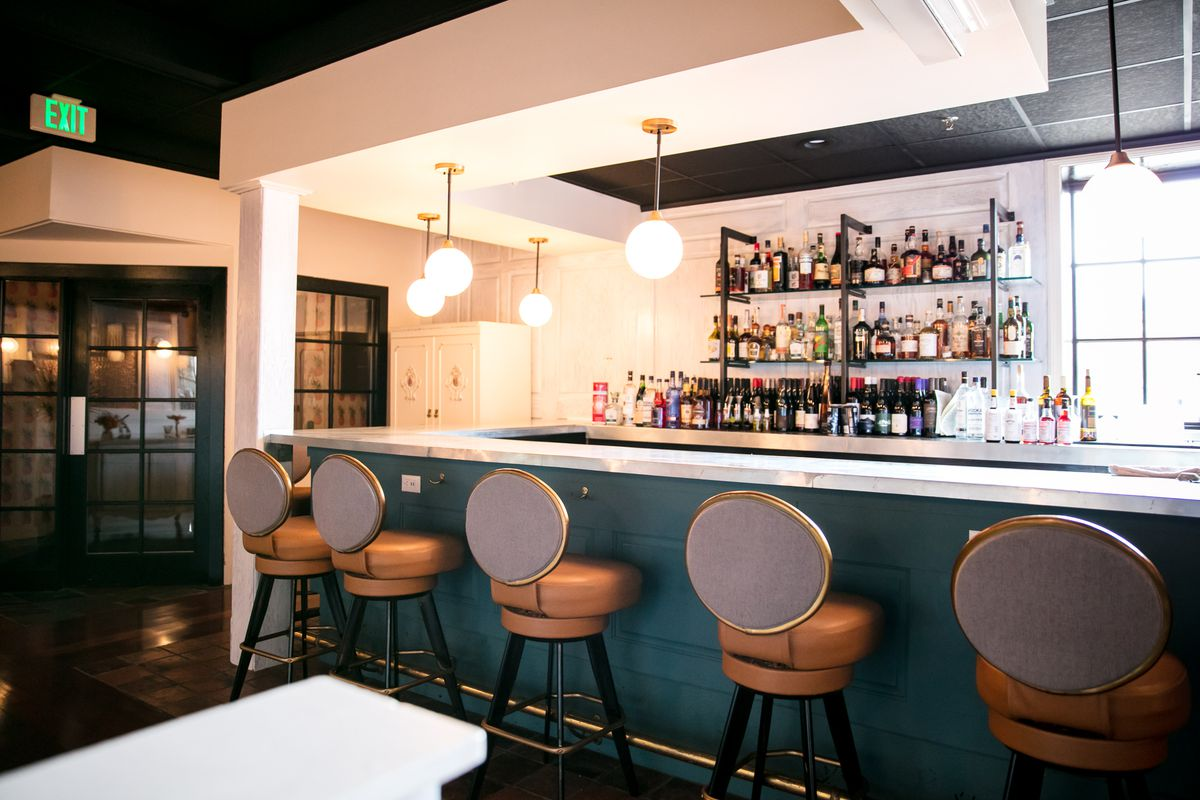 A blue green bar with upholstered bar chairs with round backs at Lady of the House.