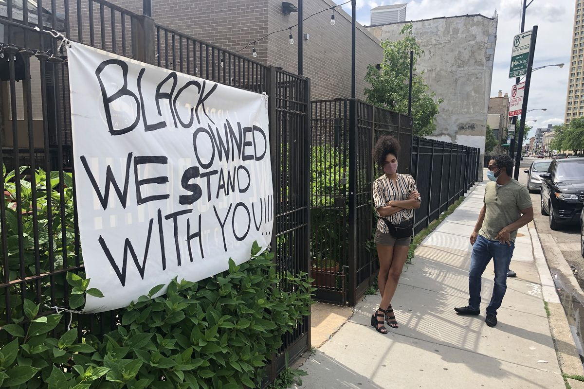 Two people stand outside a black fence where a pro-Black Lives Matter sign hangs.