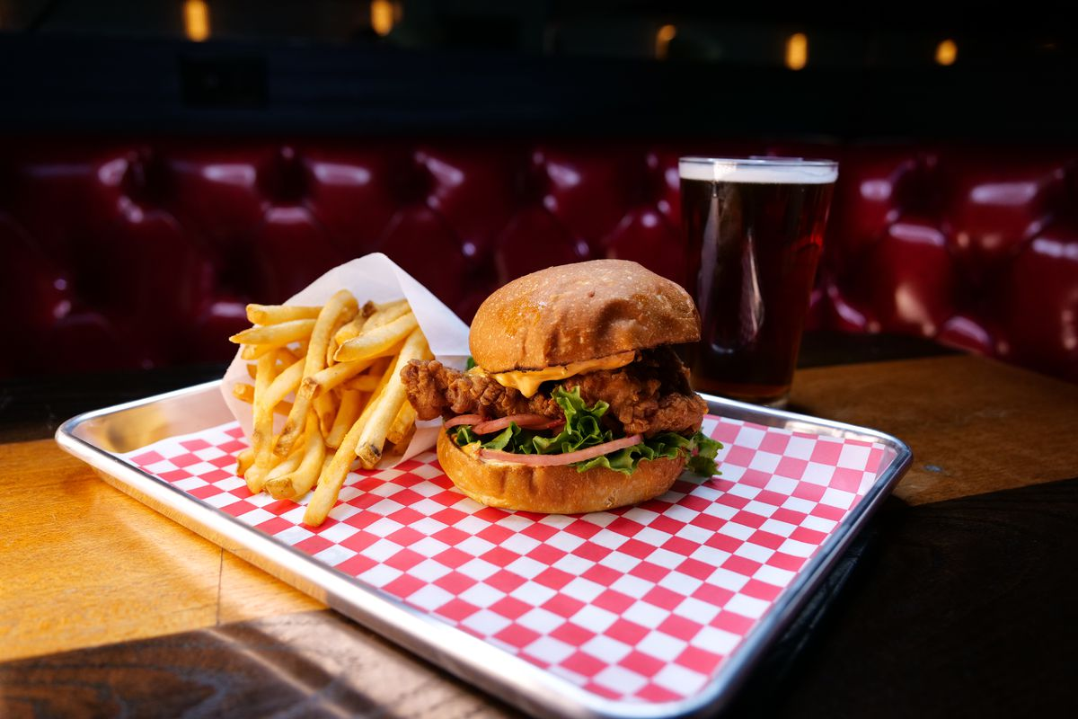 A fried chicken sandwich on a tray at a booth inside a bar