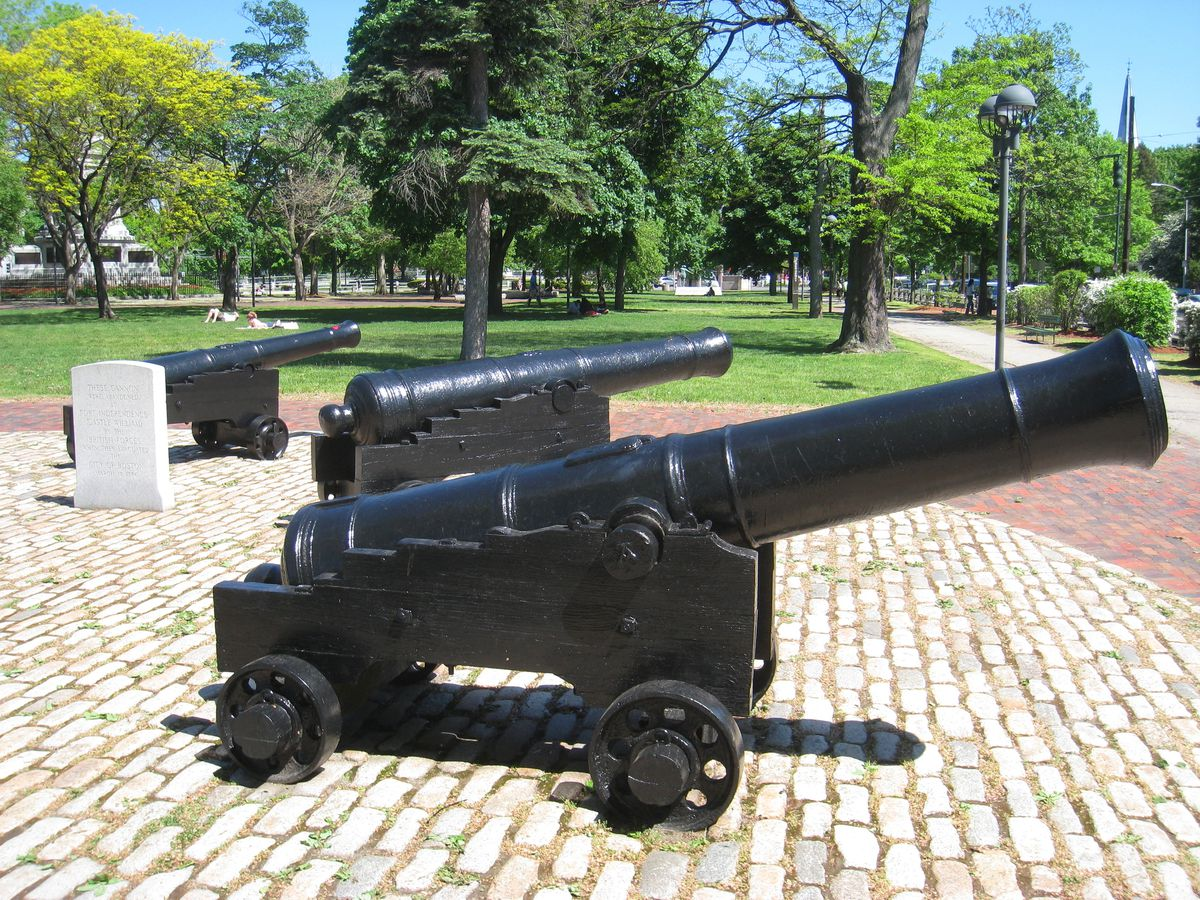 Three vintage cannons arrayed in a public park.