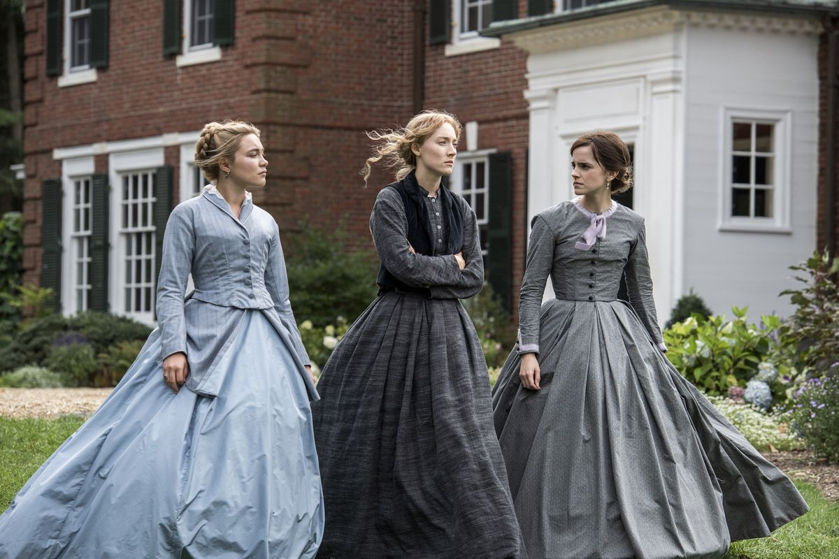three little women walk across a mansion yard in big 19th century dresses