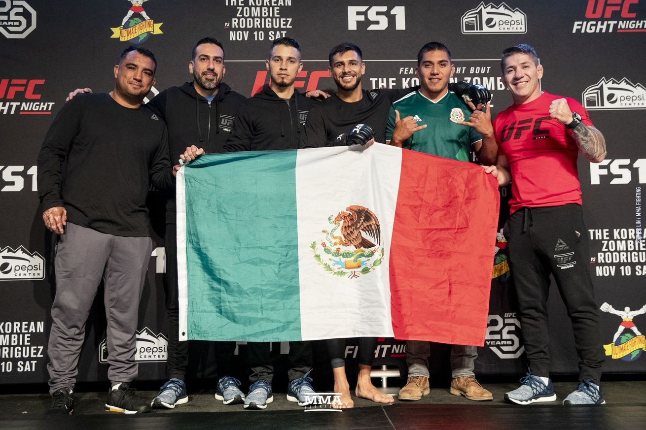 Yair Rodriguez poses with the Mexican flag at the UFC Denver open workouts.