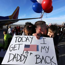 Chief Warrant Officer 2 Nathan Kruse hugs daughter Heidi and son Mason as soldiers from Detachment 2, 101st Airborne Division (Air Assault) return to Utah on Friday, Nov. 18, 2016, following an 11-month deployment to Iraq.