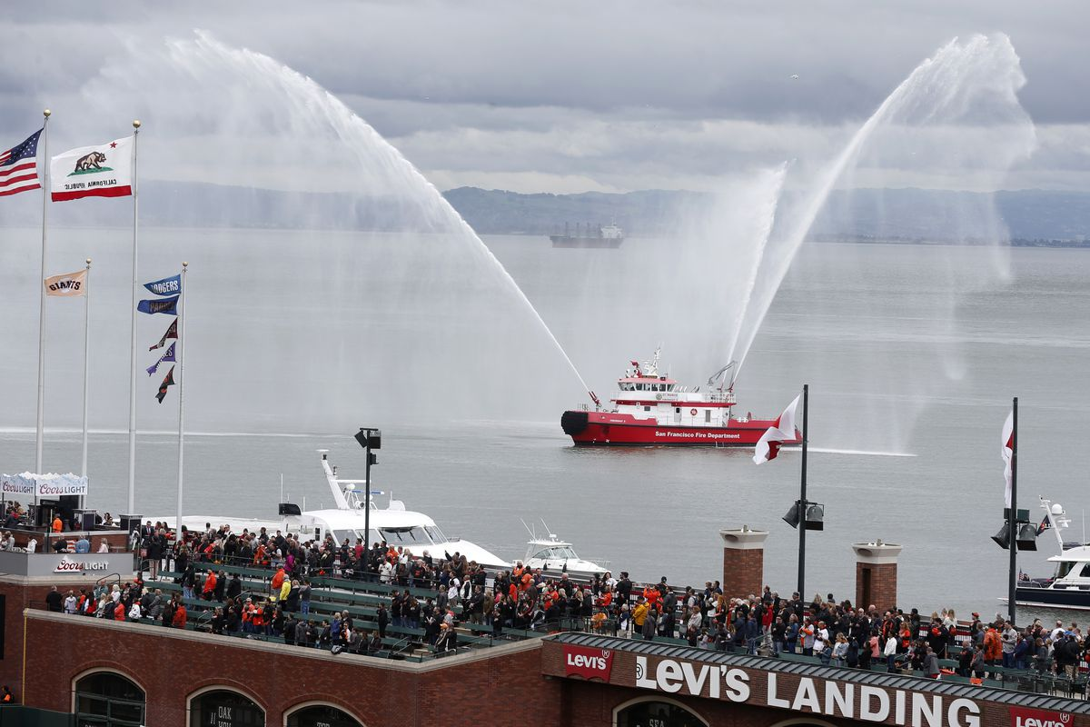 The San Francisco fireboat St. Francis sprays water high in the air from McCovey Cove during the playing of the national anthem before the Giants home opener at Oracle Park in San Francisco, Calif. on Friday, April 5, 2019.