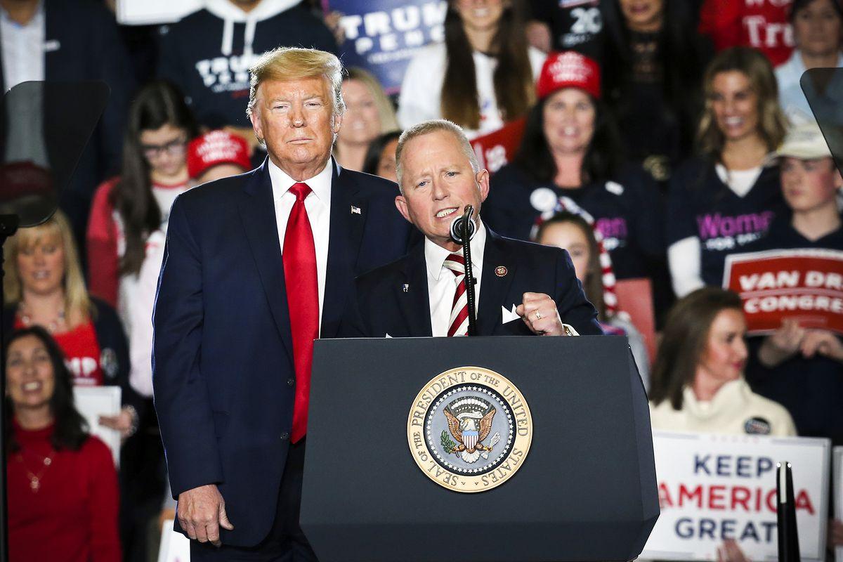 Rep. Jeff Van Drew speaks during a Trump campaign rally as President Donald Trump is seen standing behind him.