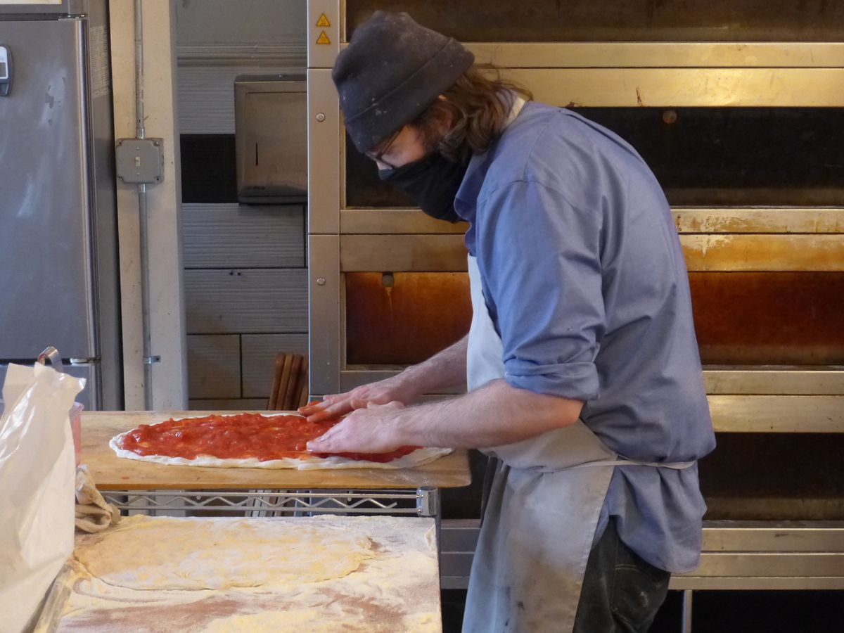 A man in an apron with mask and stocking cap leans over a pizza topped with tomatoes.