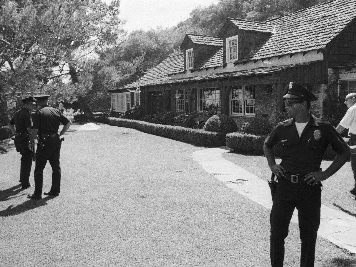 Police officers stand guard outside the house of Sharon Tate. There is a house and lawn in the background. There is a body covered with a sheet on the ground in front of the house.
