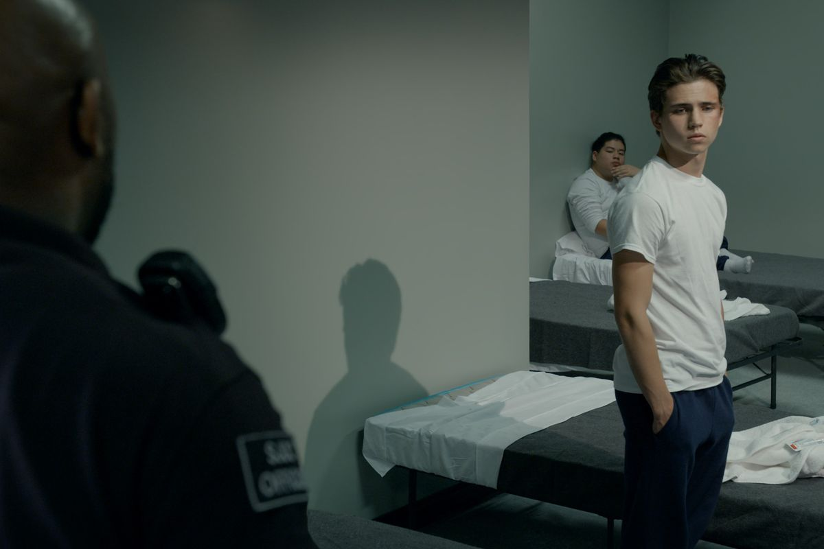 Robbie Keene (Tanner Buchanan) standing by his prison cot with hands in his pockets, looking away from a guard in the foreground.