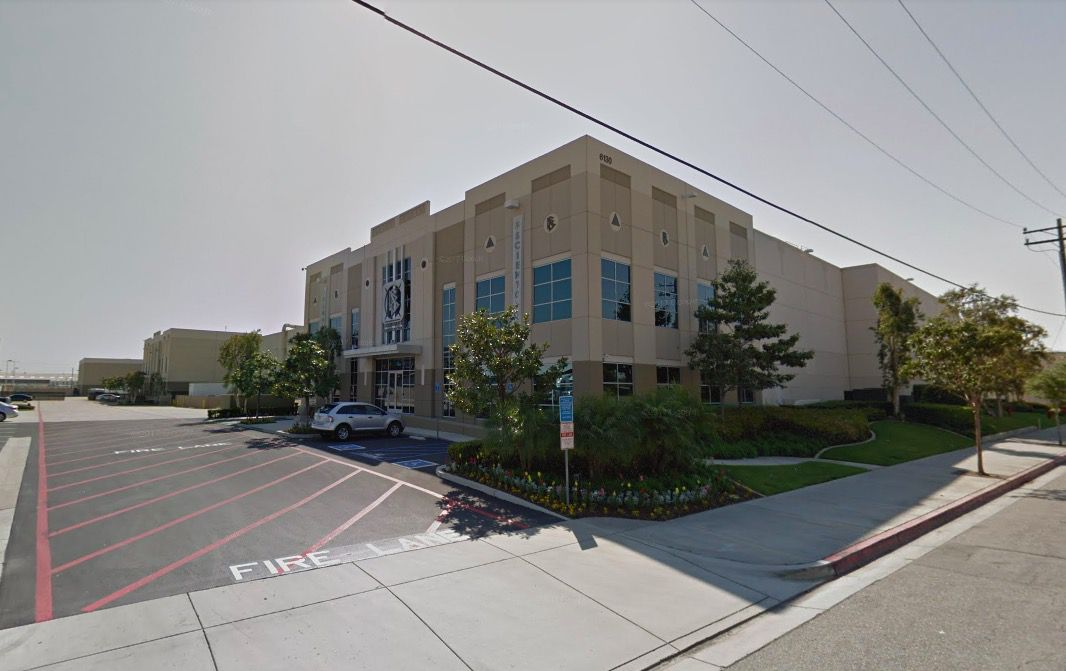 The exterior of the Scientology distribution center in Commerce, California. The facade is tan and there is a parking lot to the side of the building.