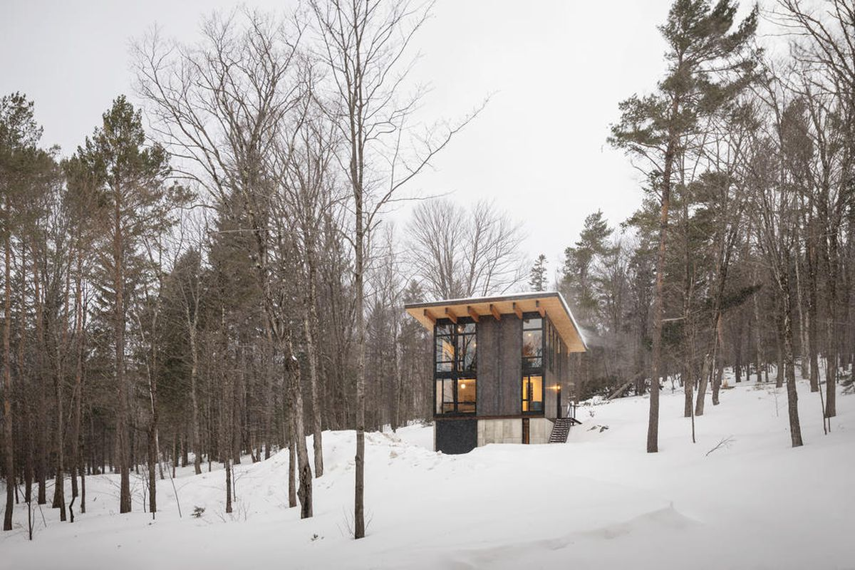 Square-shaped wooden cabin in snowy woods.