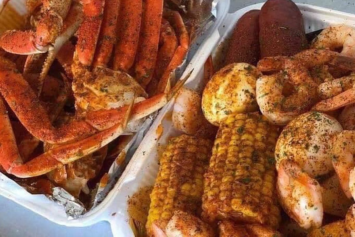 A plate of snow crab legs, with sides of shrimp, sausage, potatoes and corn on the cob.
