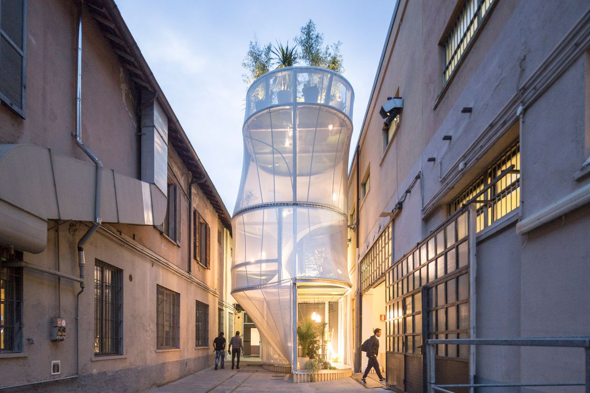 A narrow, cylindrical, multi-level, modular structure featuring mesh walls and a plant-topped roof rises in a small courtyard.