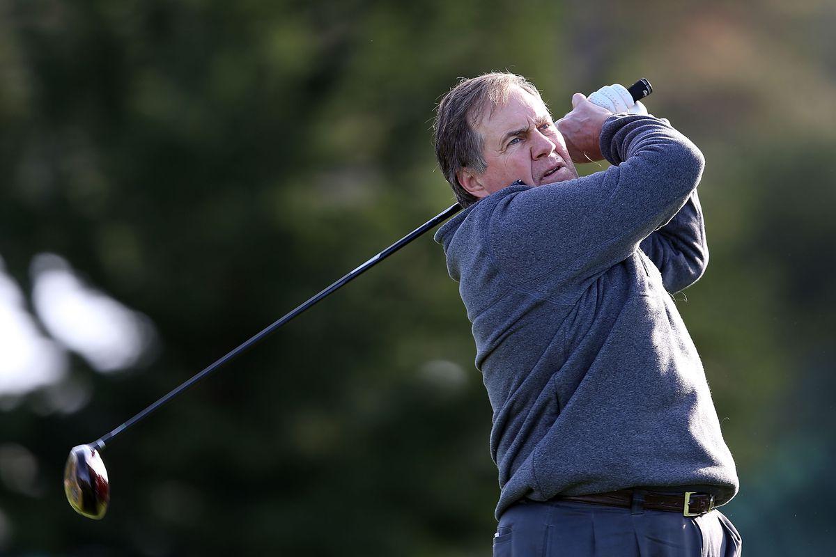 Bill Belichick arrogantly swings a golf club.