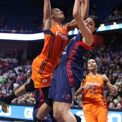 Connecticut Sun's Jasmine Thomas (5) is fouled by Washington Mystics' Bria Hartley (8).