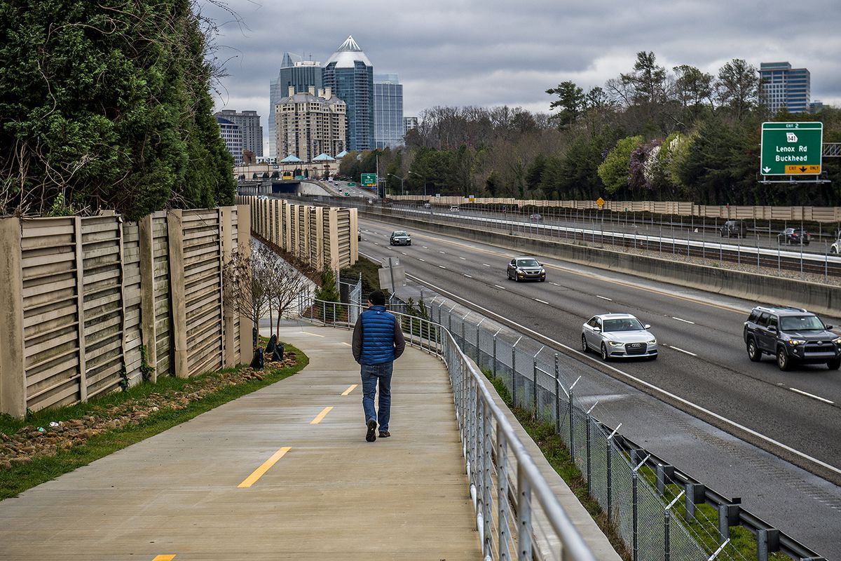 A man walks along PATH 400 in Buckhead in mid-March, chilly.