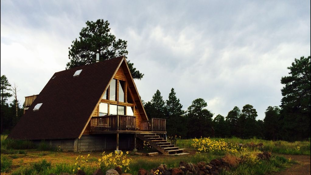 An A-frame house in Arizona. The facade is wooden with a staircase and deck. The house is surrounded by trees and wildflowers.