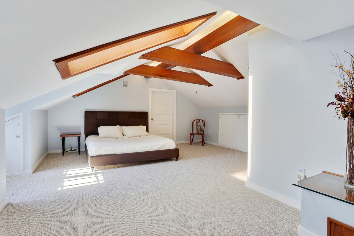 A sparely furnished bedroom with a white bed, while walls and overhead beams.