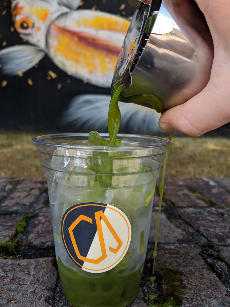 A cocktail tin pouring a bright green iced matcha latte infused with vanilla and mint into a plastic to-go cup filled with ice cubes
