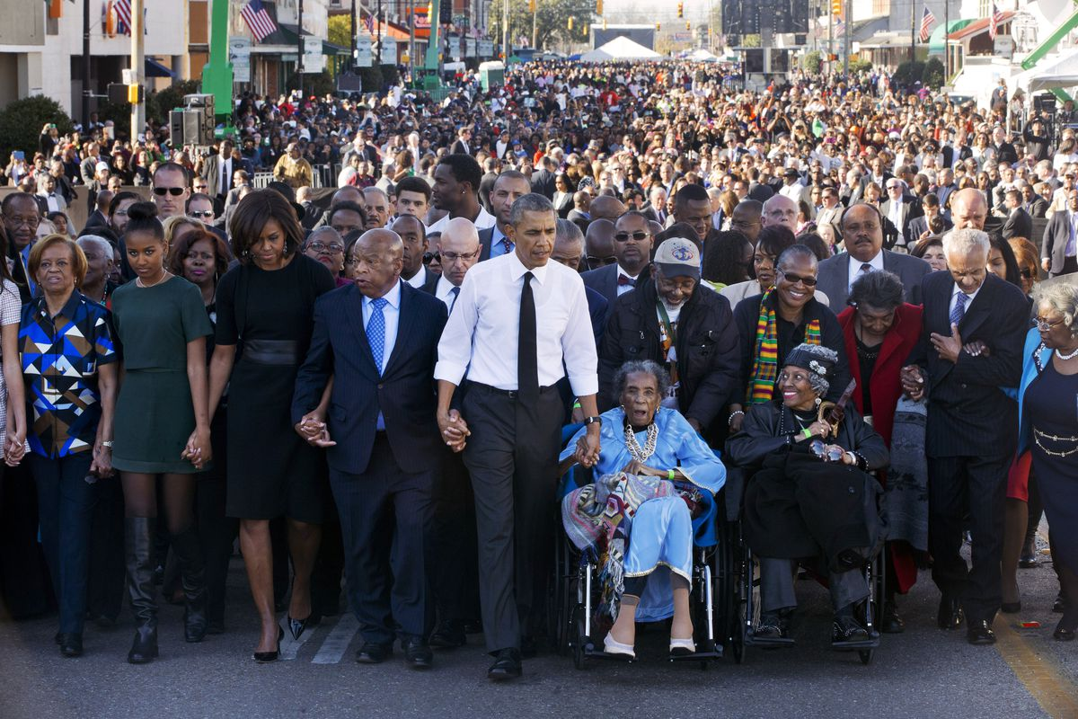 """In this March 7, 2015, file photo, President Barack Obama, center, walks as he holds hands with Amelia Boynton Robinson, who was beaten during """"Bloody Sunday,"""" as the first family and others including Rep. John Lewis, D-Ga., left of Obama, walk across the Edmund Pettus Bridge in Selma, Ala., for the 50th anniversary of """"Bloody Sunday,"""" a landmark event of the civil rights movement."""