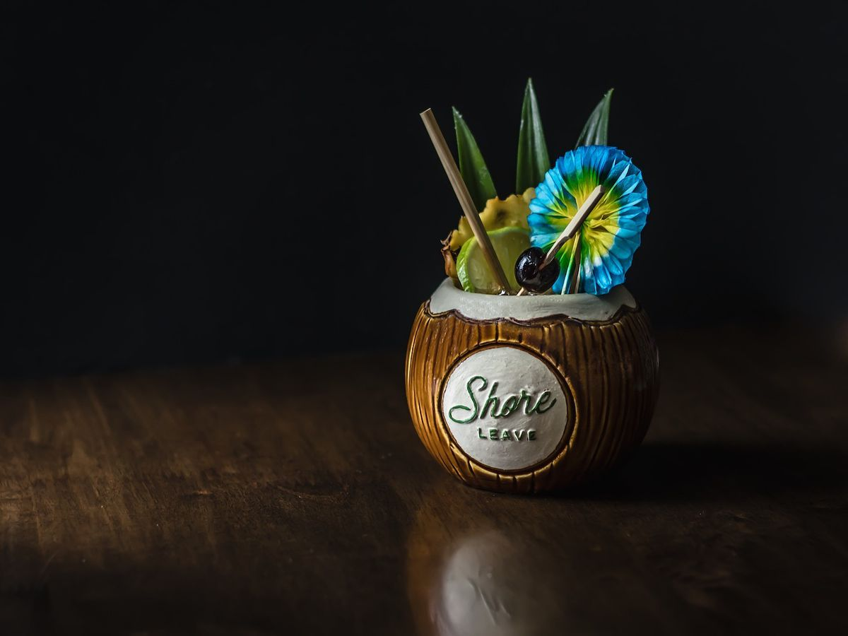 The Shore Leave cocktail —in a signature Shore Leave coconut Tiki mug —sits isolated on a dark surface