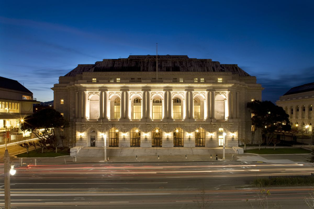 The exterior of the War Memorial Opera House in San Francisco. The facade is white with large arched windows and columns. It is evening and the sky is dark blue.