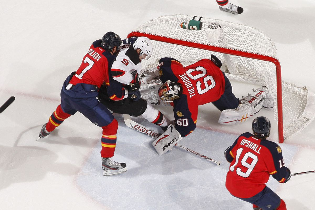 Crashing the net is usually a good idea on offense.  Zach Parise, with help from Dmitry Kulikov, shows that it can be taken to an extreme. (Photo by Joel Auerbach/Getty Images)
